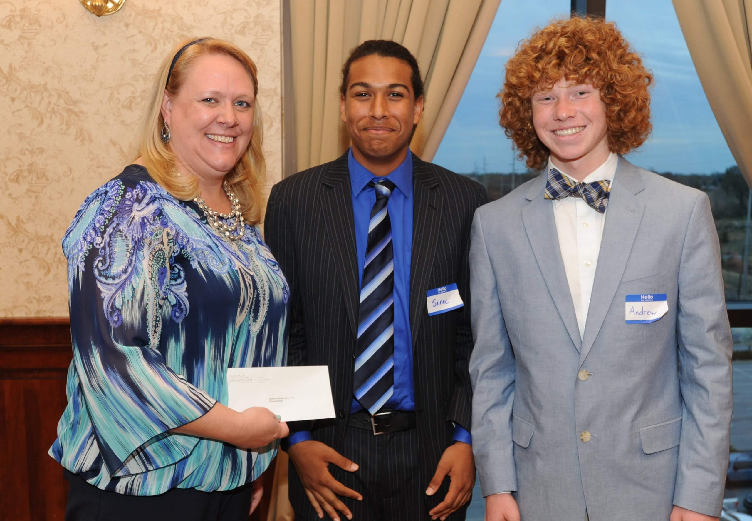 Christy Pennington of Delaware Guidance Services for Children and Youth accepts a Youth Philanthropy Board grant from Smyrna High School seniors Serac McClenton (center) and Andrew Morrison.