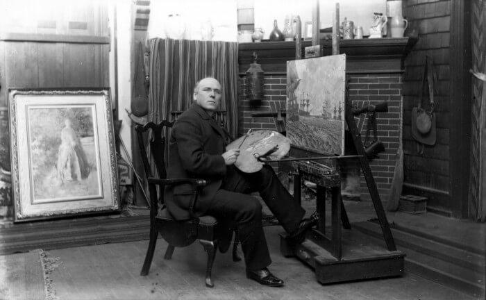 The artist Howard Pyle painting in his studio