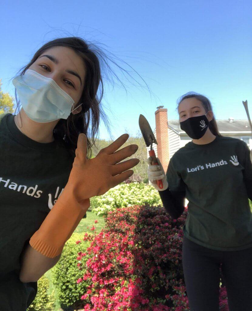 Two college-age girls wearing Lori's Hands t-shirts while volunteer gardening